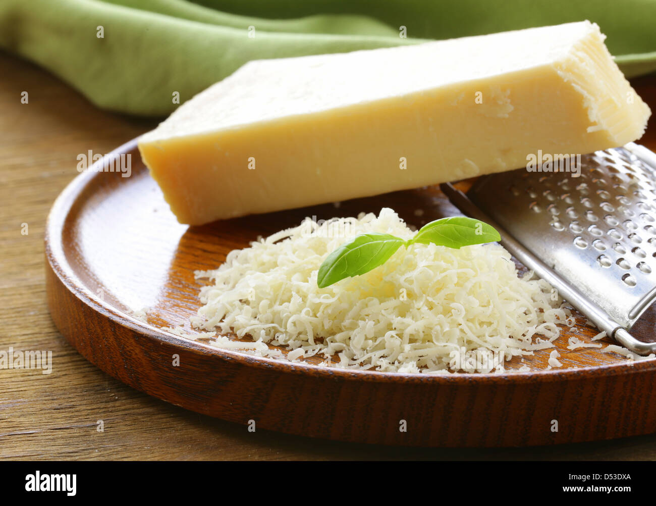 grated parmesan cheese and metal grater on wooden plate - Stock Image
