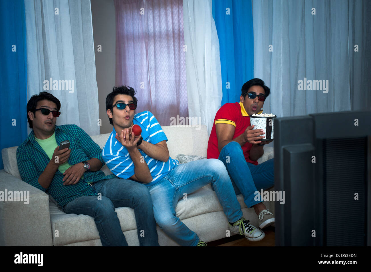 Friends watching cricket match on the television with 3-D glasses at home - Stock Image