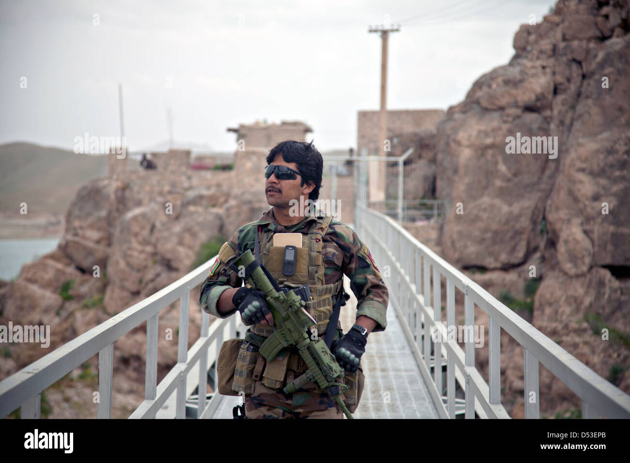 An Afghan National Army special operations forces soldier guards a hydro-electric dam march 22, 2013 in Helmand - Stock Image