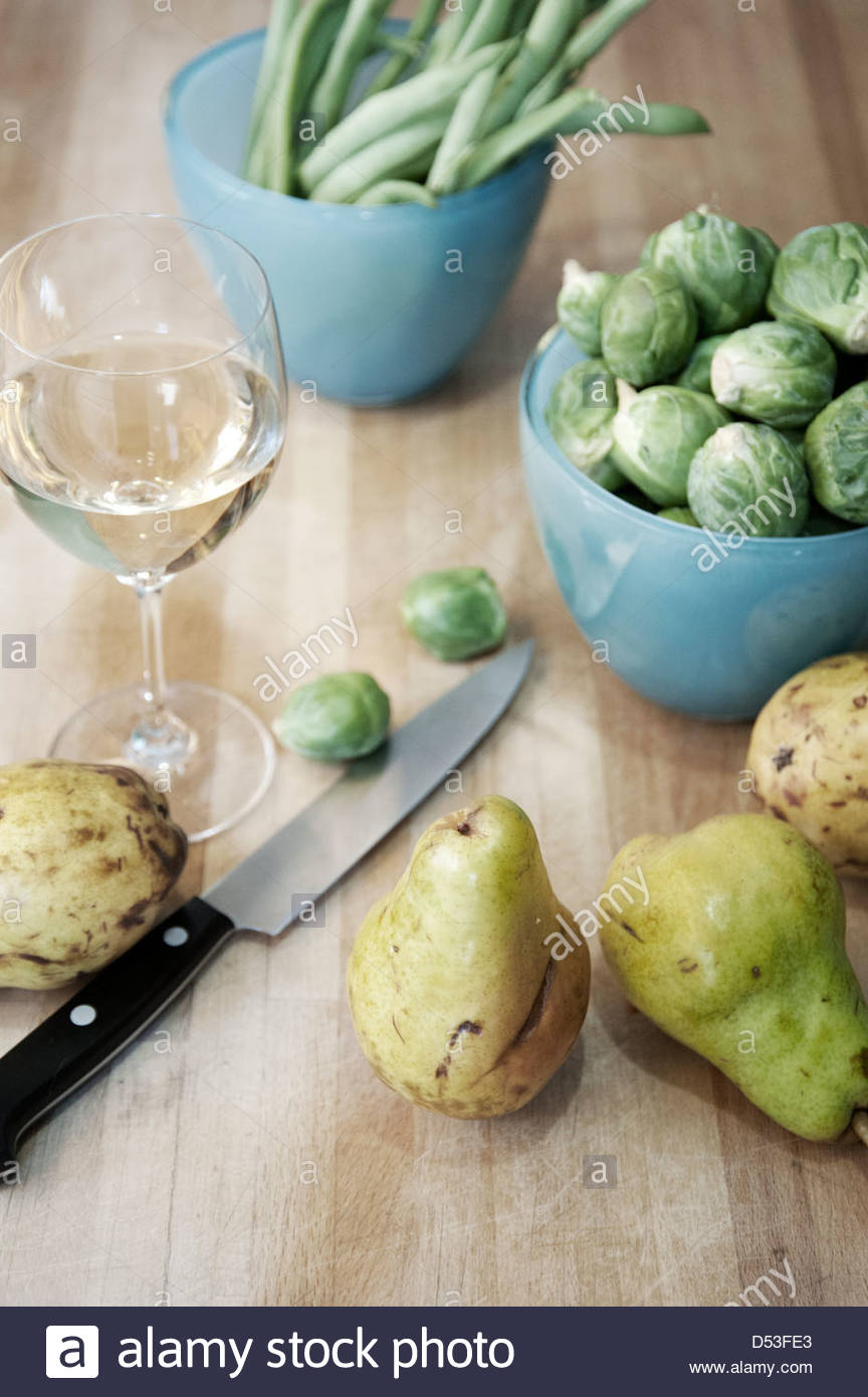 Dinner preparation with a glass of wine, brussels sprouts, pears and green beans on butcher block counter top - Stock Image