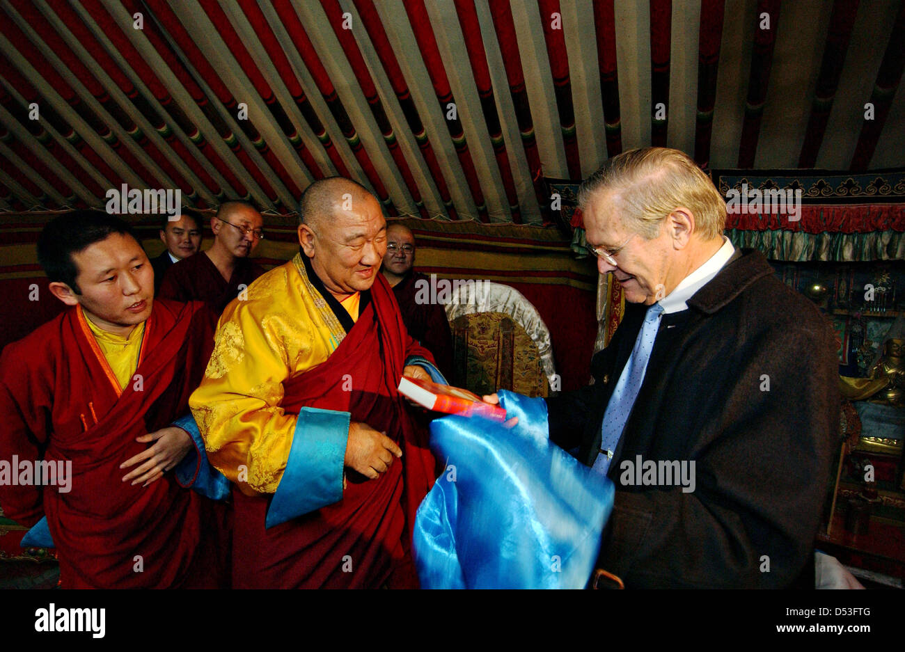 US Secretary of Defense Donald Rumsfeld accepts a gift during a tour of the Gandan Monastery Library lead by Head - Stock Image
