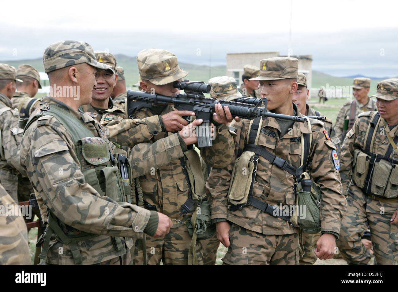 Mongolian armed forces soldiers examine a U.S. Marine Corps issued M-4 carbine as part of Khaan Quest 2009 at the - Stock Image