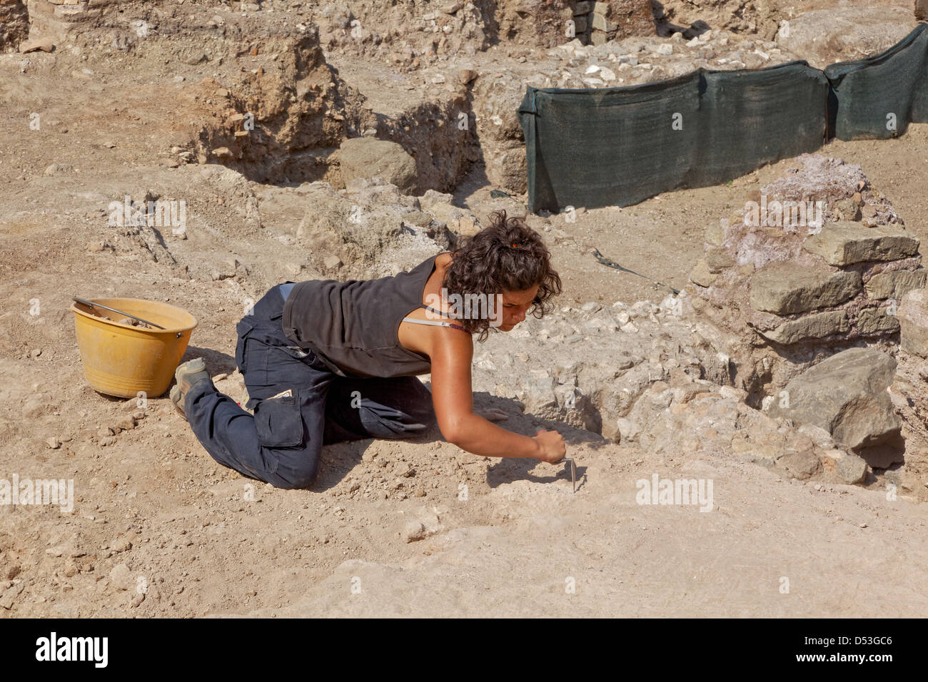 Archaeologist excavating a Roman site adjacent to the  Arch of Constantine, Rome, Italy - Stock Image