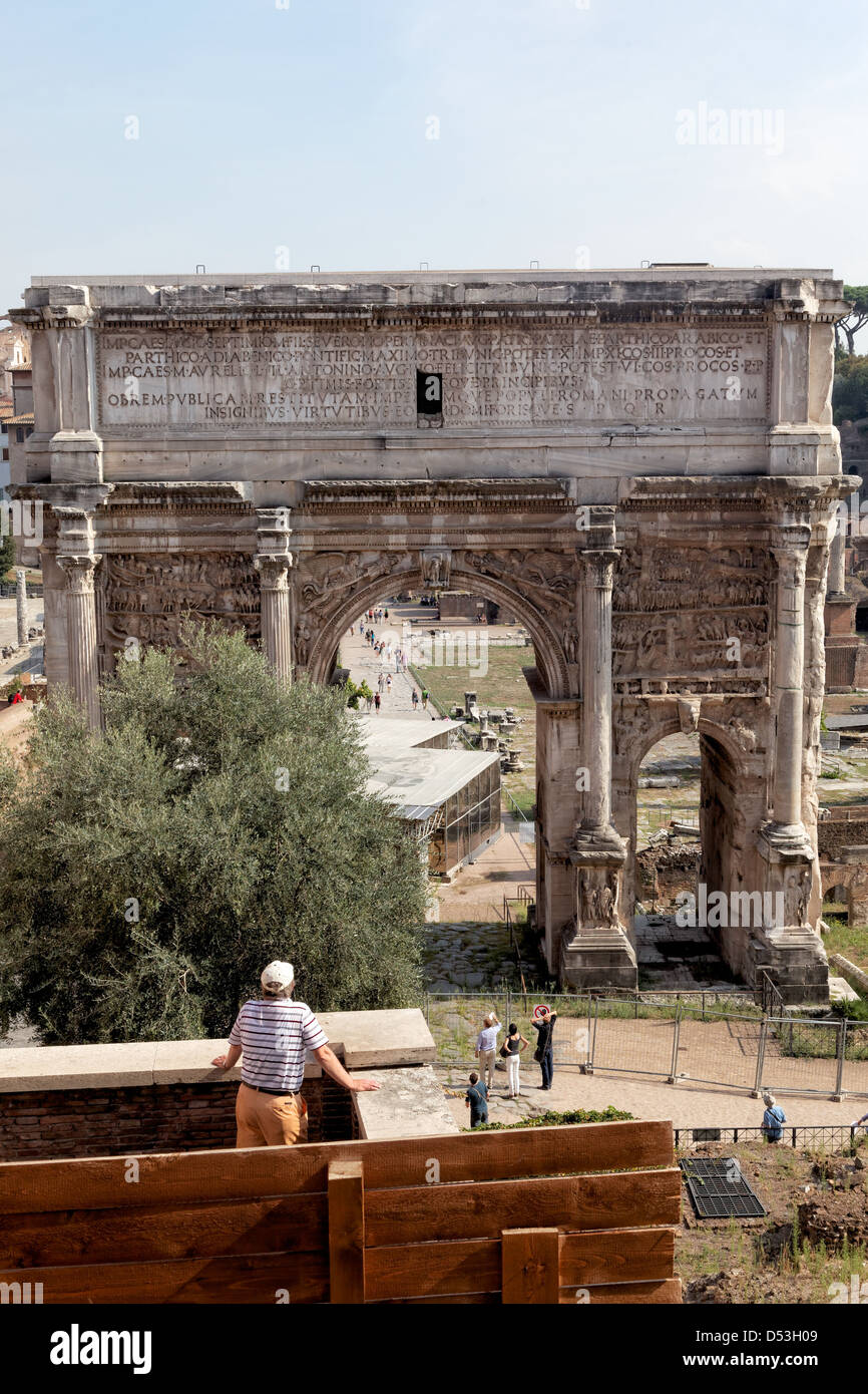 Tourists look at the triumphal arch of the Emperor Septimus Severus in the ruins of the Roman Forum, Rome Italy - Stock Image