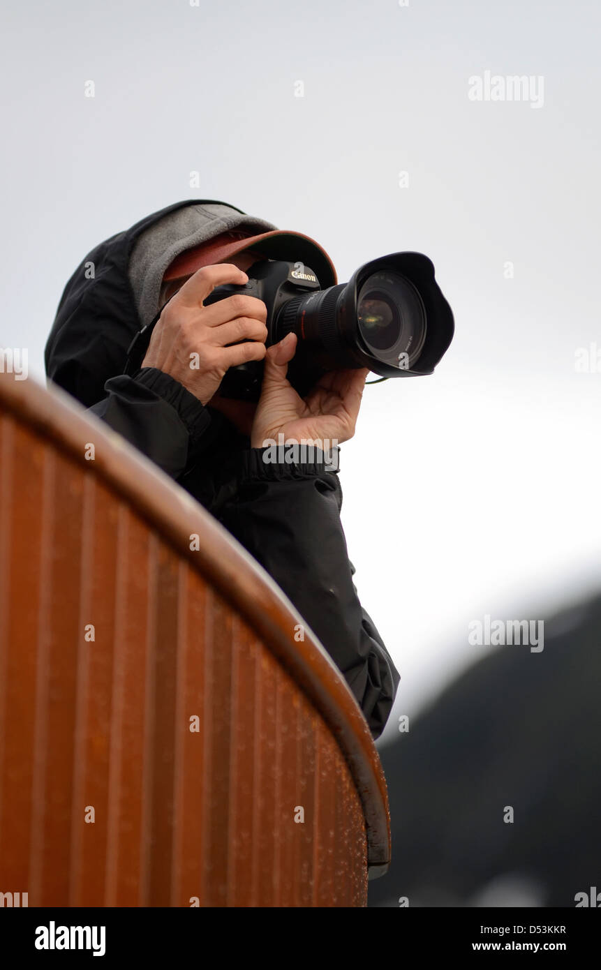 Photographing from the deck of a small tour boat in Glacier Bay, Alaska. - Stock Image