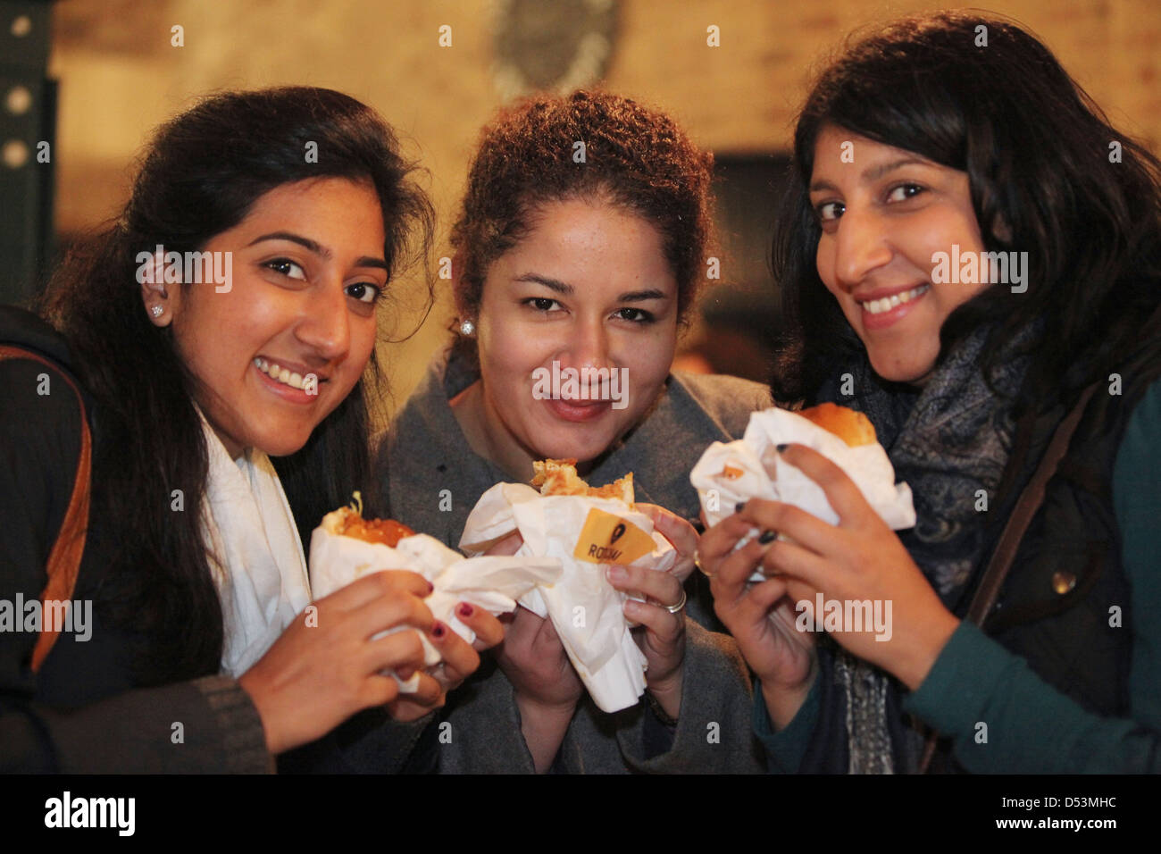 people eating food at Feast food festival at Tobacco Dock, London UK, February 2013 - Stock Image