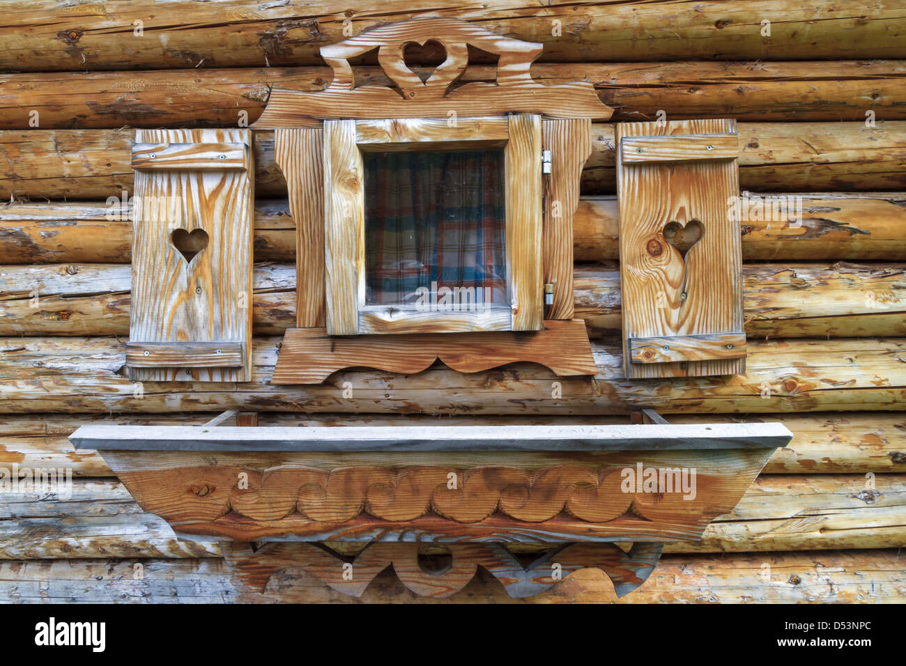 Window with heart shutters of a wooden log cabin in the European Alps - Stock Image