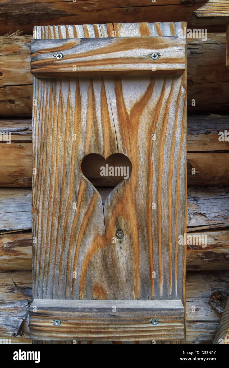 Window shutter with heart of a wooden log cabin in the European Alps - Stock Image