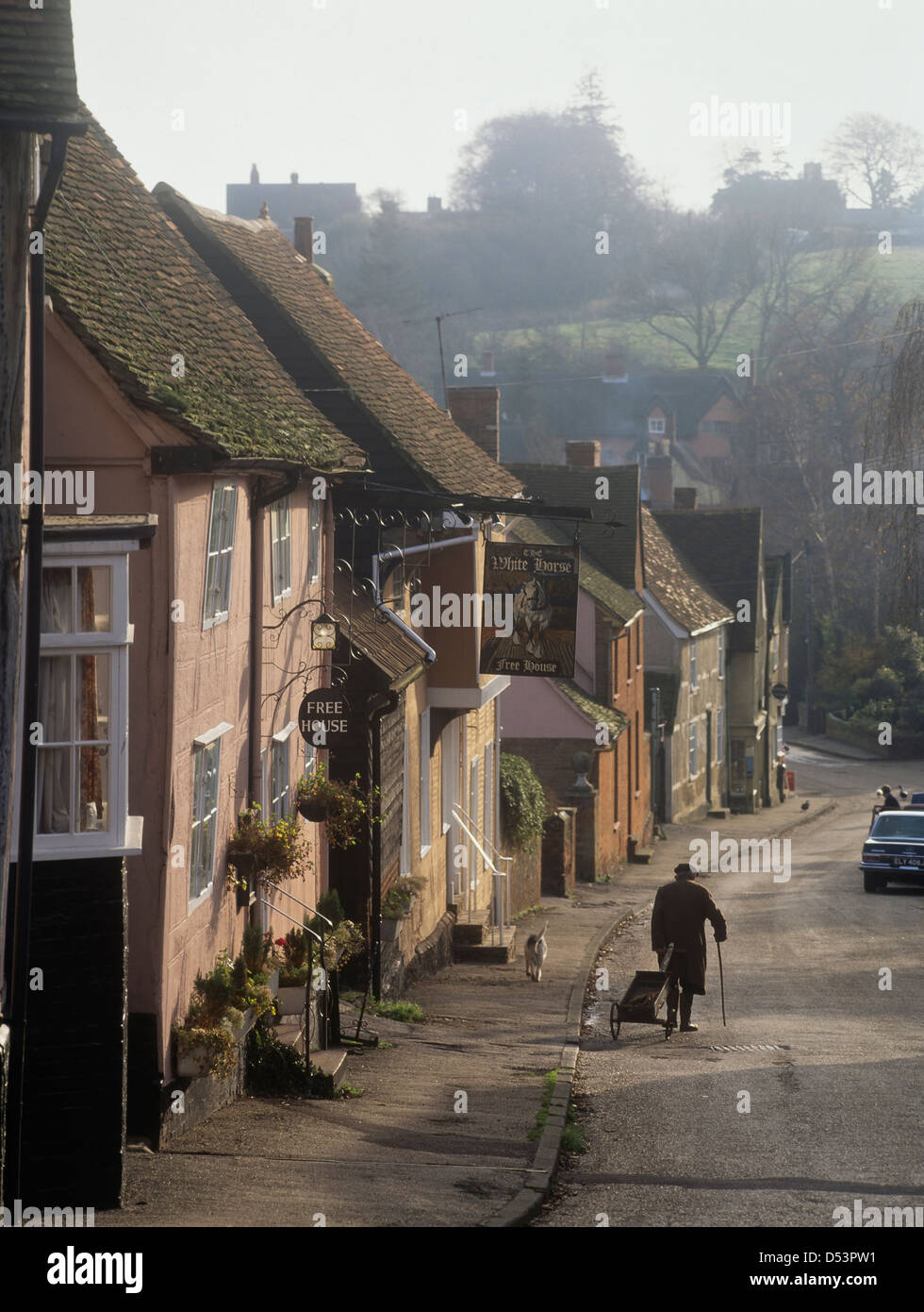 Old man with his dog walking down the main street in Kersey village, Suffolk, UK. Circa 1980 - Stock Image