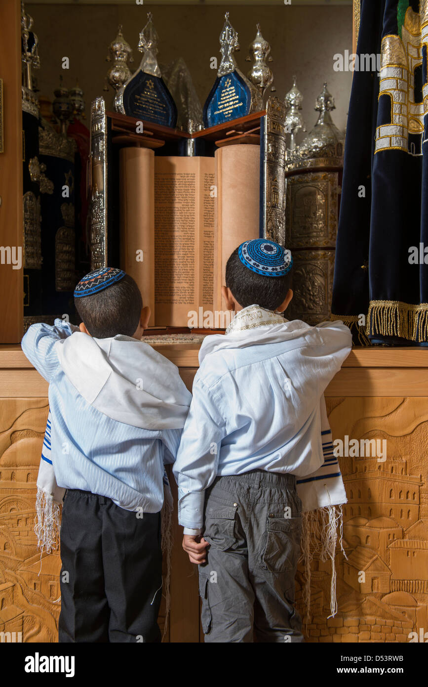 two jewish kids in front of holy scripts in a synagogue - Stock Image
