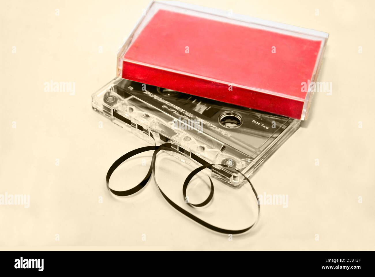 Two old cassette tapes with and without plastic cases on a sepia background. - Stock Image