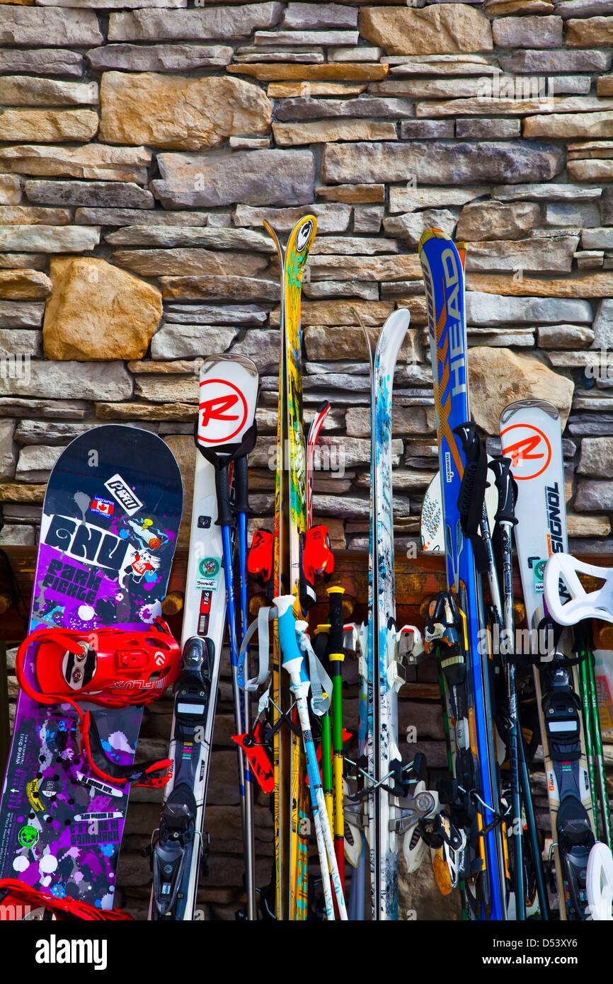 Ski equipment leaning against a rock wall on Whistler mountain - Stock Image