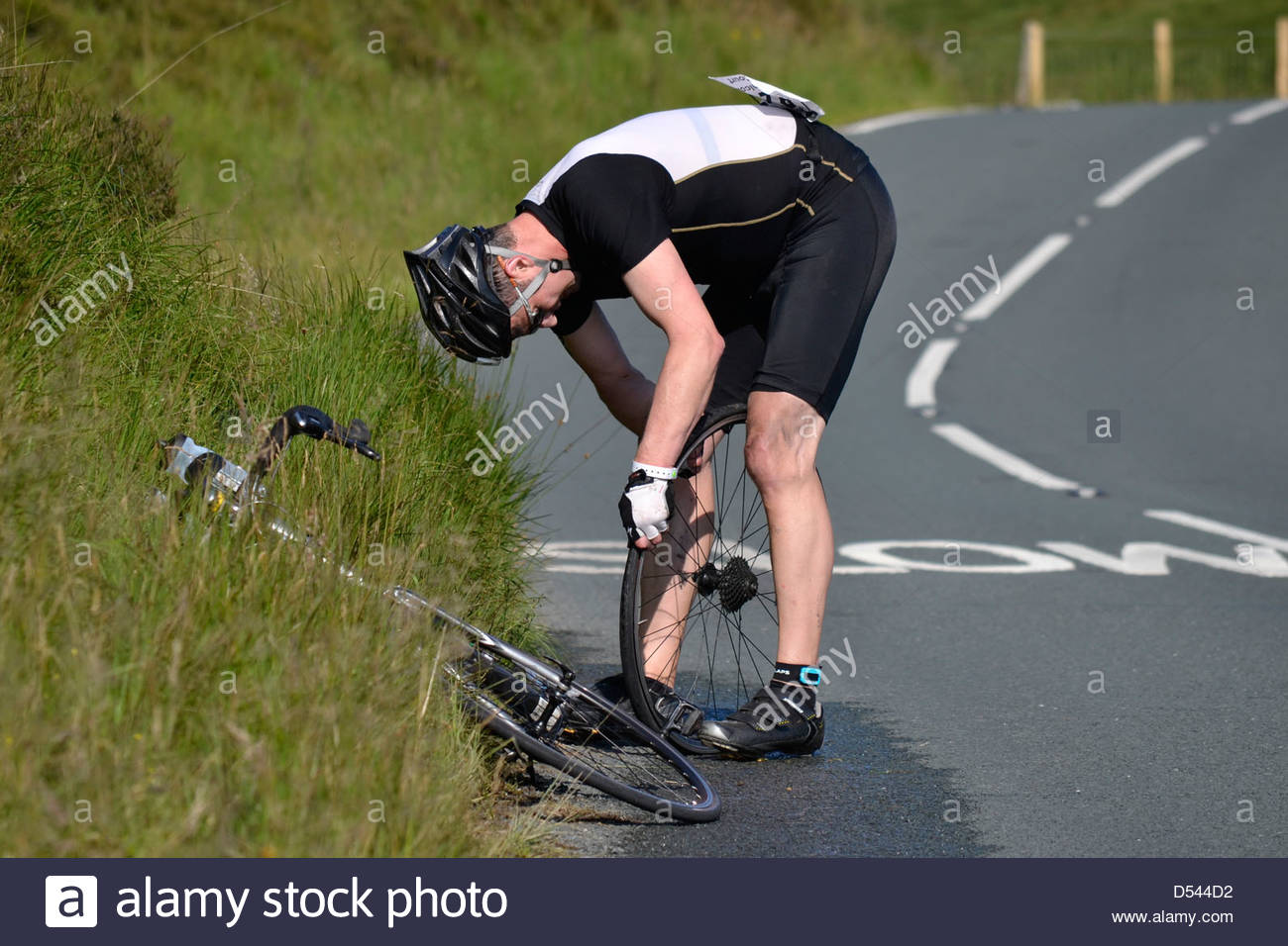 A competitor in the Bolton Ironman, 2012, has to stop by a slow sign to repair a puncture. - Stock Image