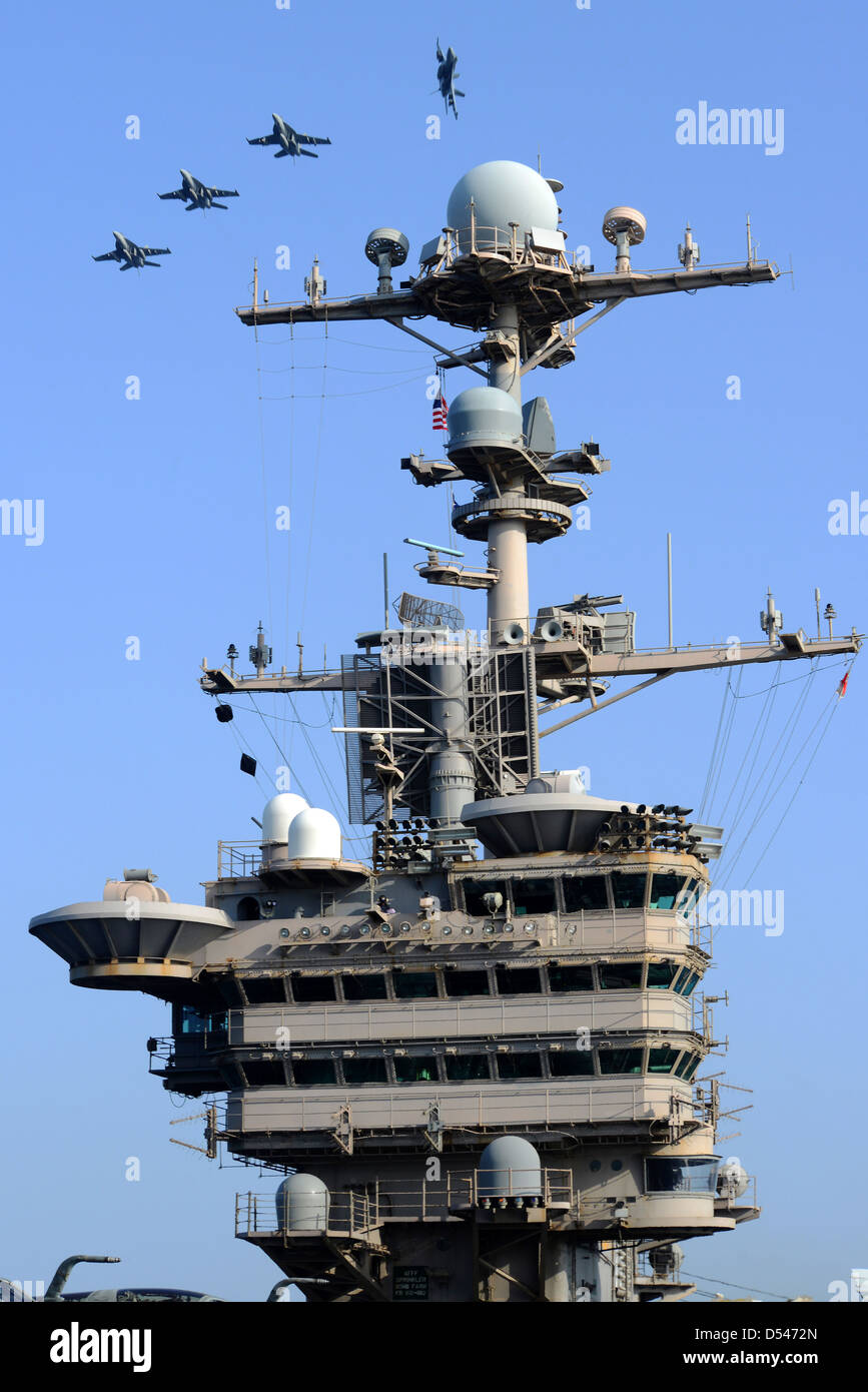 US Navy aircraft breaks formation over the flight deck of the aircraft carrier USS John C. Stennis in the Arabian - Stock Image