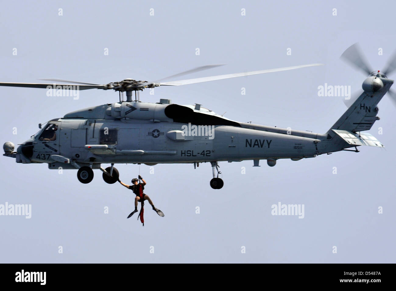A US Naval Air crewmen is raised from the water by a SH-60B Sea Hawk helicopter during a search and rescue exercise - Stock Image