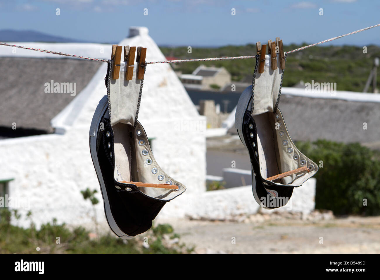 Converse All Stars hanging out to dry. - Stock Image