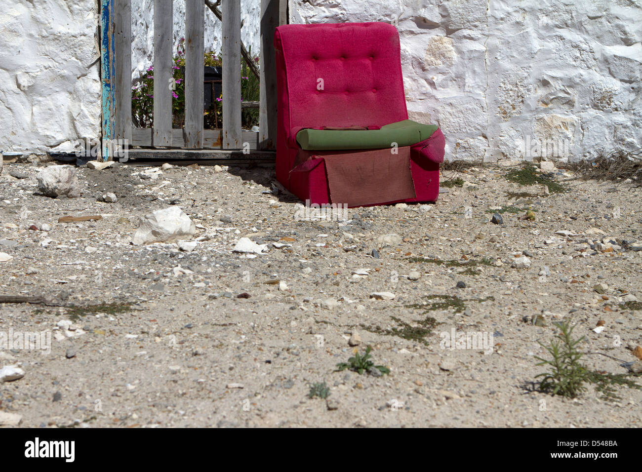 Old chair outside a house. - Stock Image