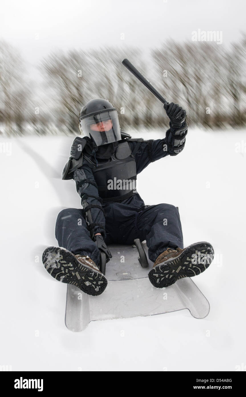 Police officer dressed in riot gear sledging on his shield in snow - Stock Image