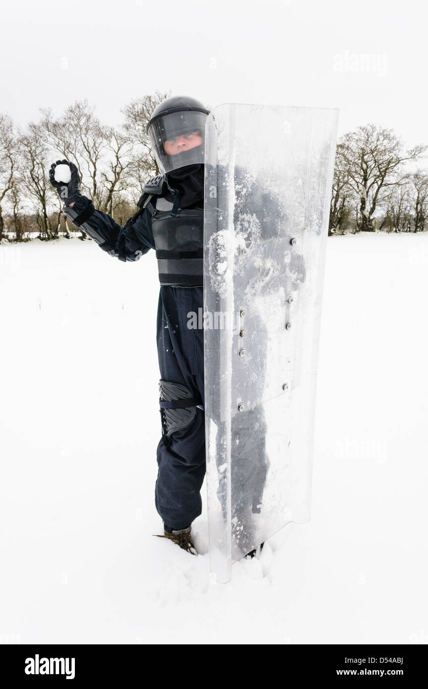 Police officer dressed in riot gear about to throw a snowball - Stock Image