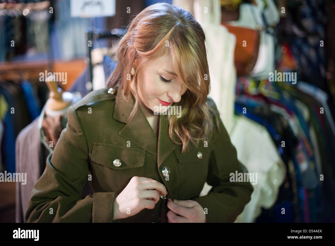 15db29a38c7 Pretty young woman buttons up and tries on an old green army jacket at a  vintage