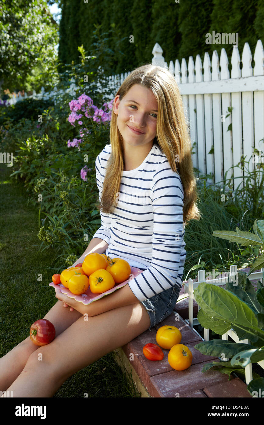Girl holding home grown tomatoes in urban garden - Stock Image