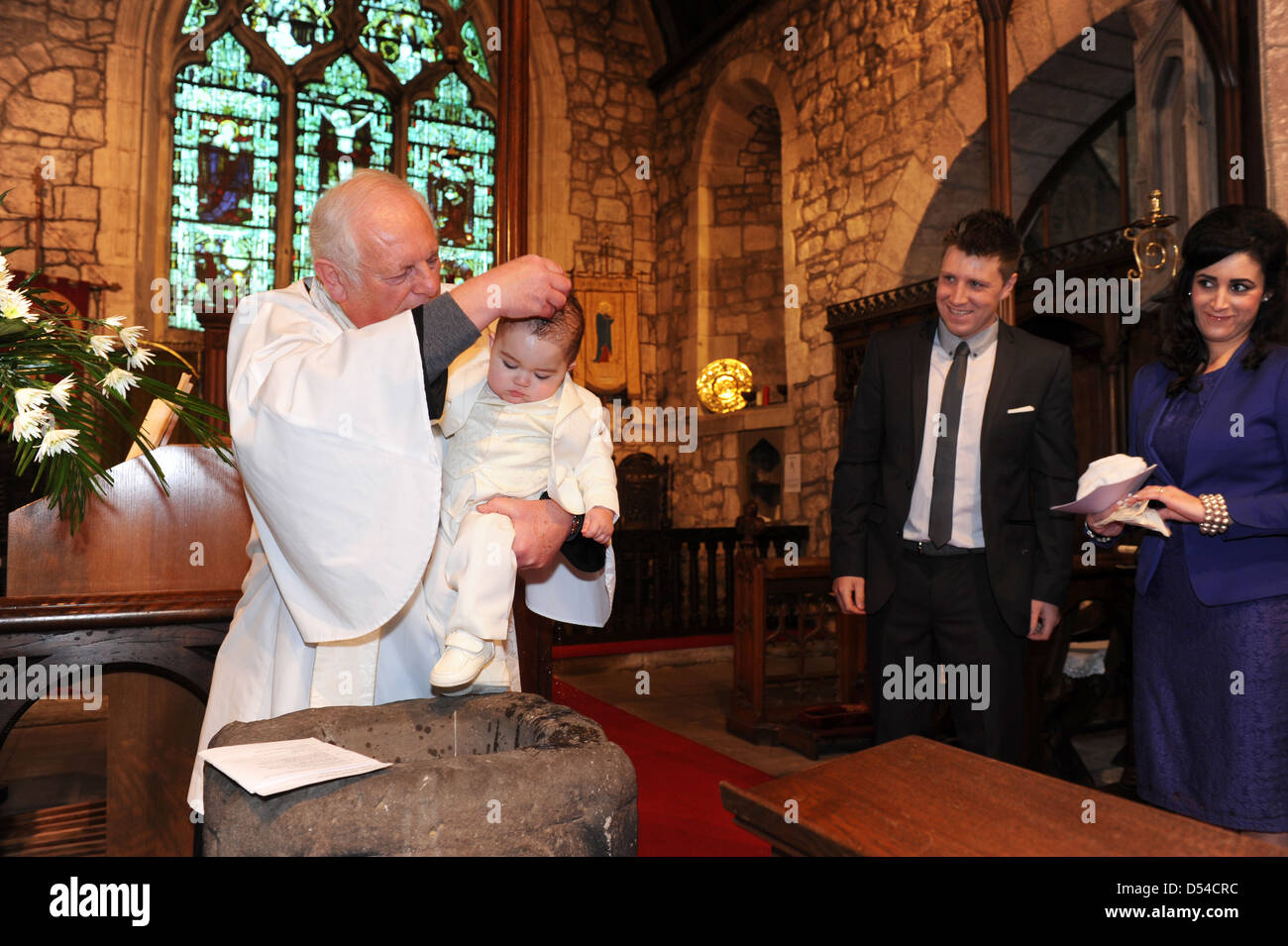 Young child being christened by a vicar and watched by the parents England Uk - Stock Image