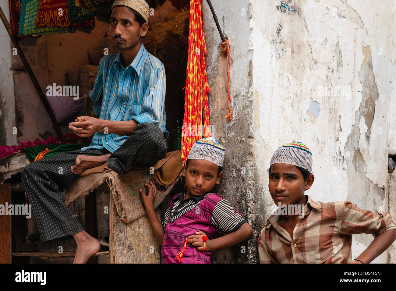 Local shopkeeper and his sons sell religious trinkets outside the mosque in Nizamuddin, Old Delhi, India. - Stock Image