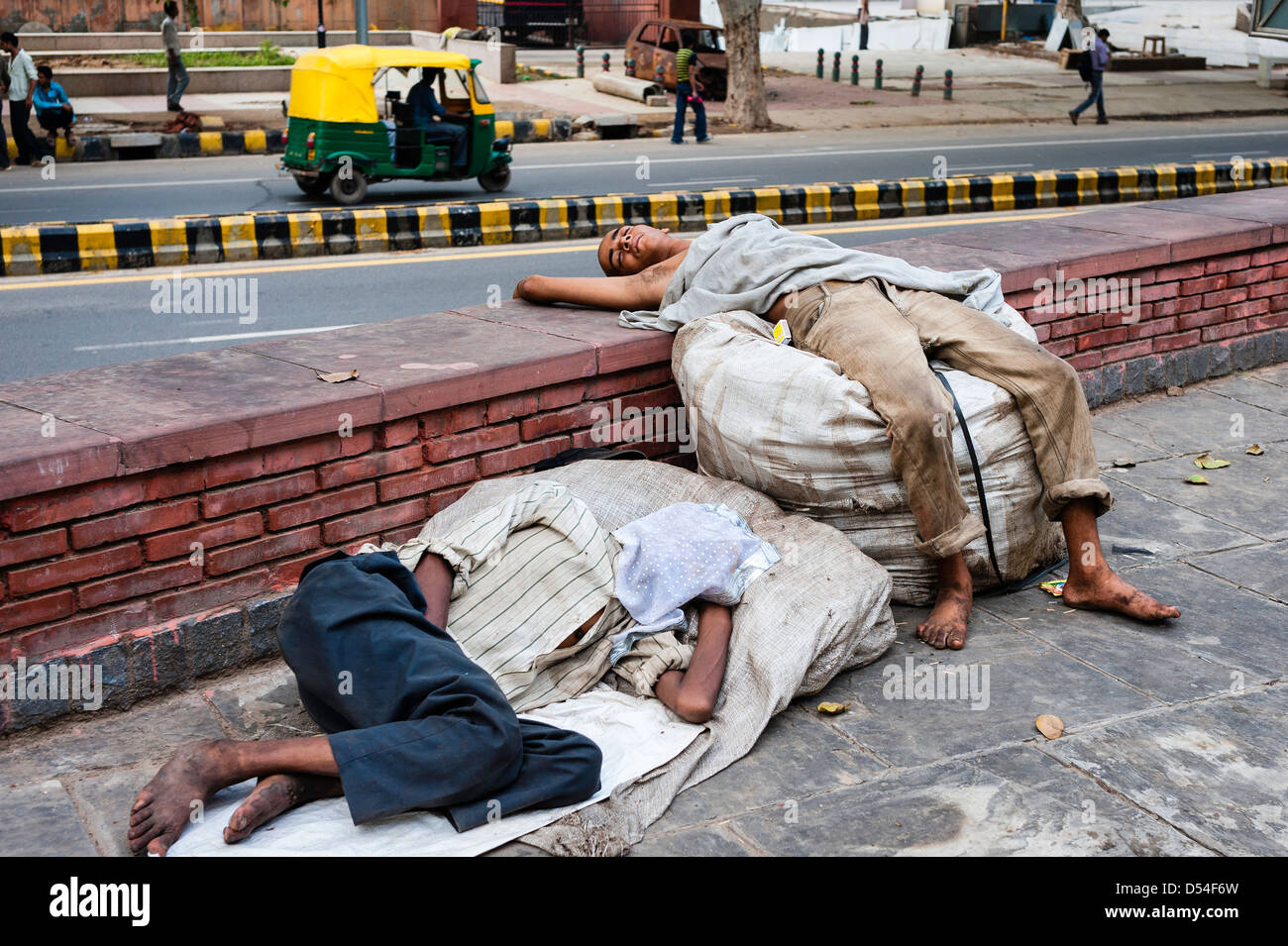 Homeless people asleep on the side of a busy road in Karol Bagh, a salubrious area of New Delhi, India. - Stock Image