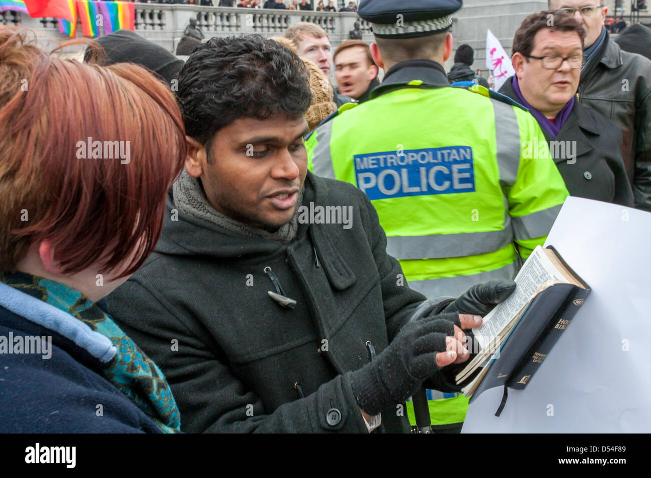 A Christian reads extracts of the bible to an LGBT rights supporter. Protesters on both sides of the argument on - Stock Image