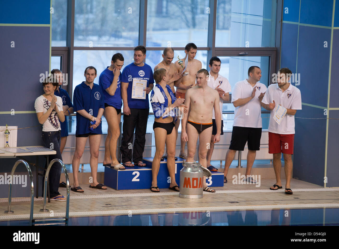 Swimmers on the podium during the awarding a relay swim. Swimming pool in Russia. Local competition of companies - Stock Image