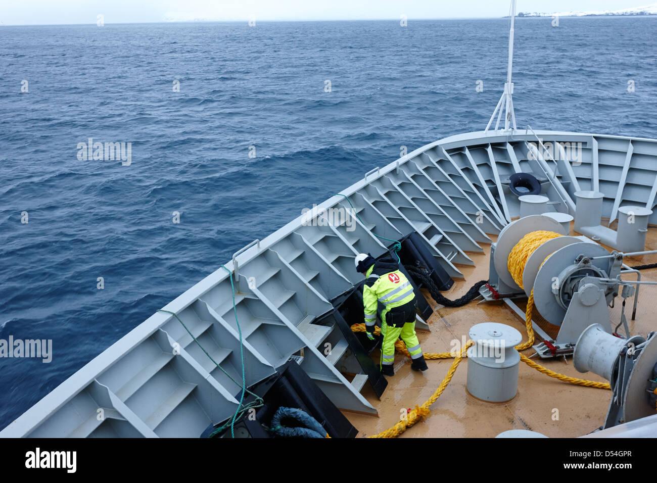 crewman working on ships ropes on board hurtigruten passenger ship sailing through fjords during winter norway europe - Stock Image
