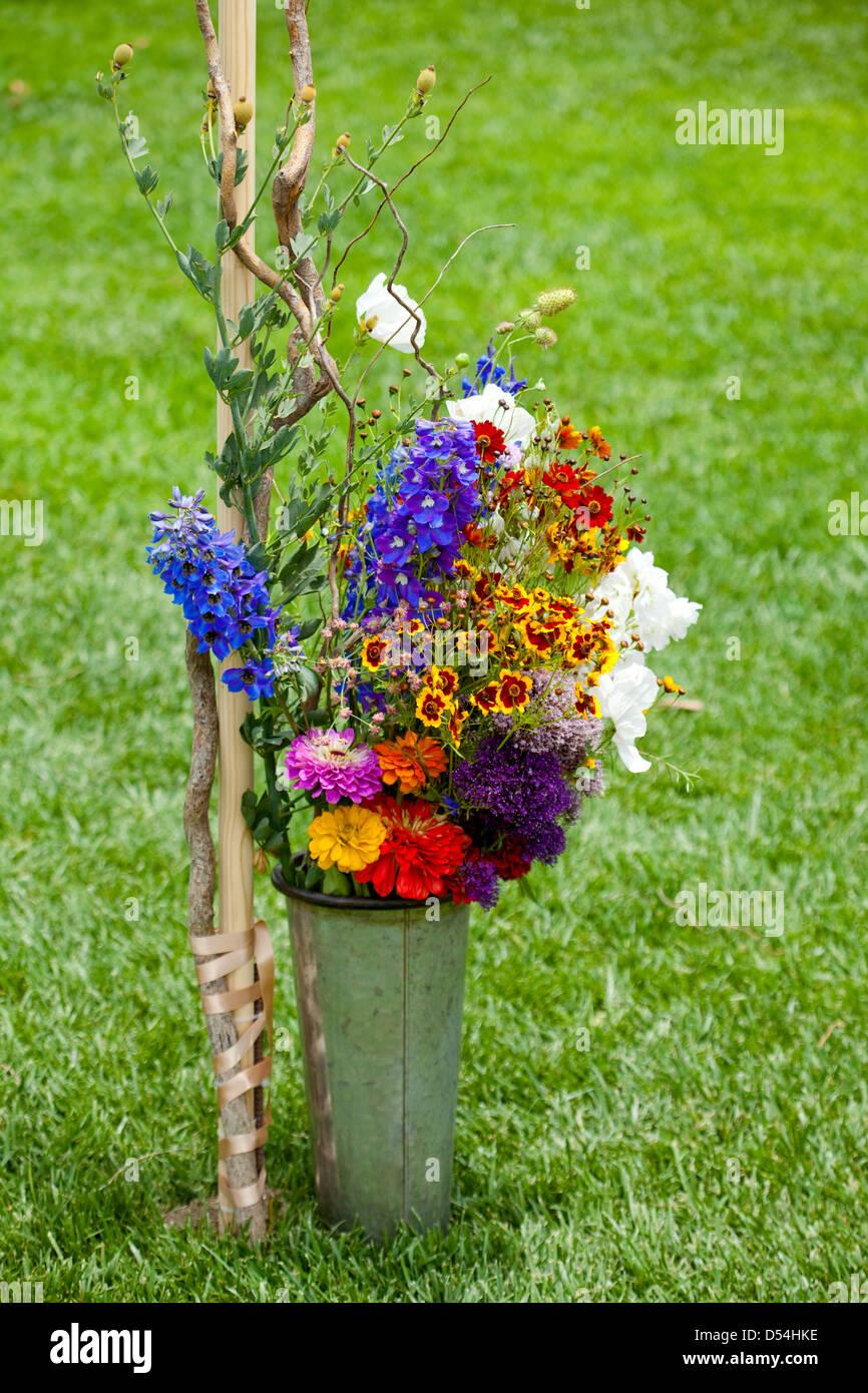 Farmers market flowers, orange, yellow, red, green, purple, green, grass, galvanized metal bucket, bambo - Stock Image