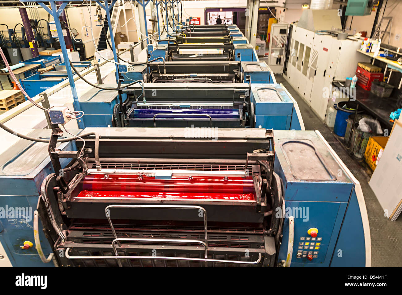 Offset litho printing press showing magenta, cyan, yellow and black inks applied from rollers, Aberystwyth, Wales, - Stock Image