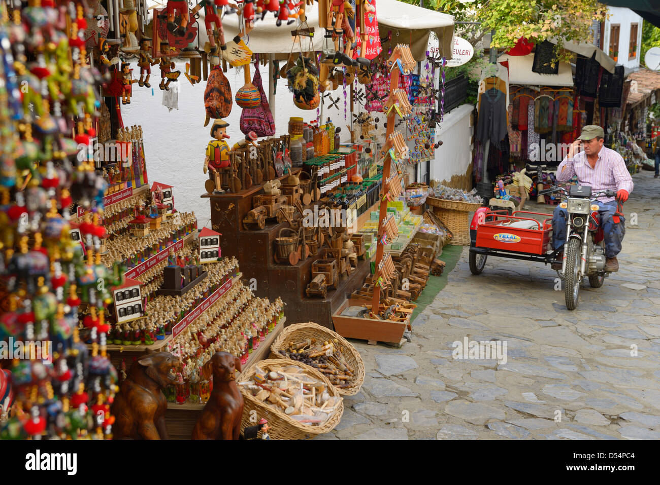 Man on bike with sidecar talking on cellphone beside gift shop at hillside village of Sirince Turkey - Stock Image
