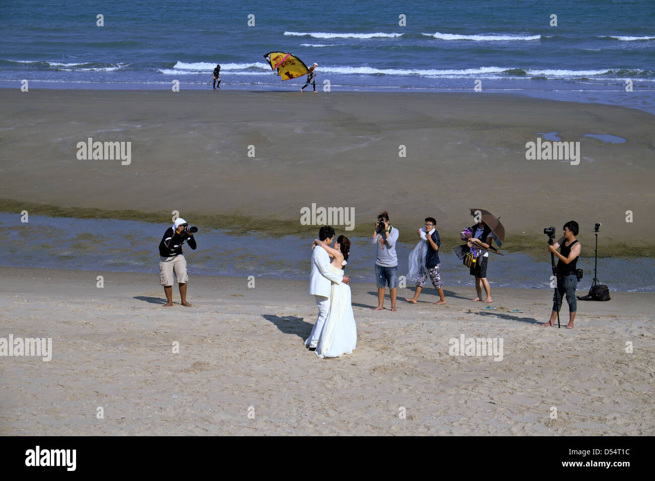 Wedding photographer. Thai beach location used for a wedding shoot with bride, groom photographer and numerous assistants. Stock Photo