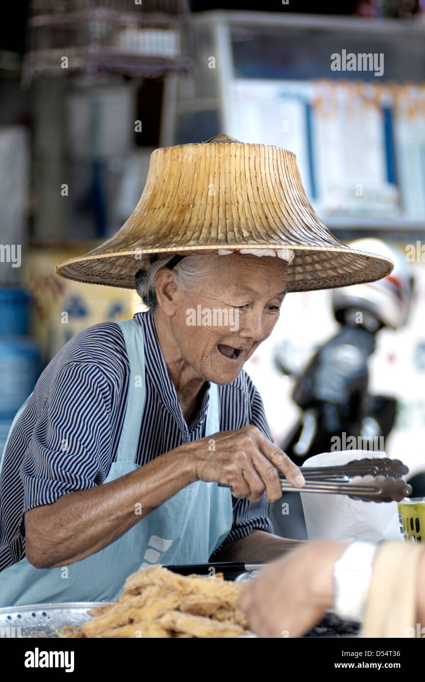 A very happy and laughing elderly Thailand street food vendor serving customers. Thailand S. E. Asia - Stock Image