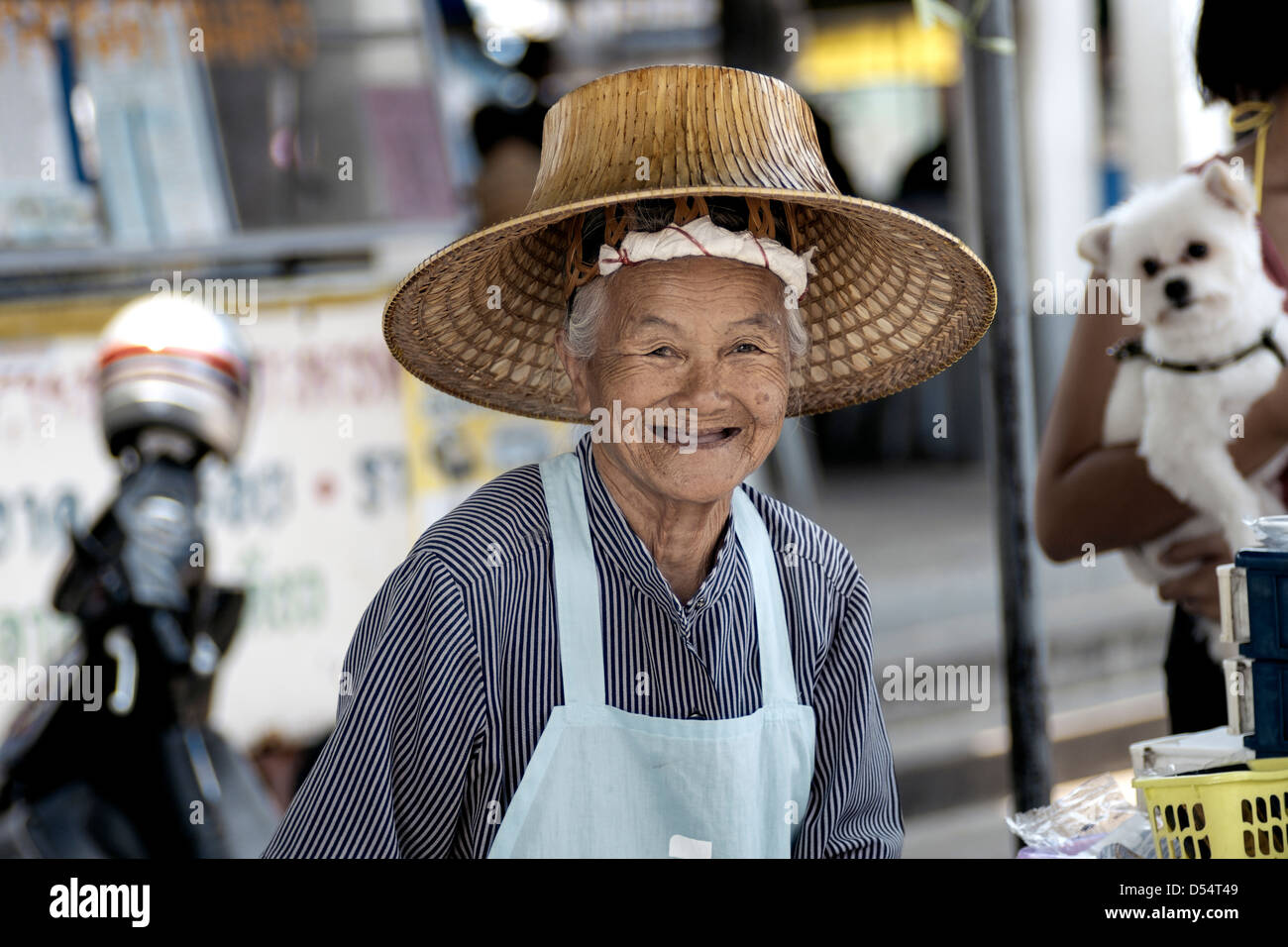 Elderly woman street food vendor, happy and smiling at her work. Thailand Southeast Asia - Stock Image