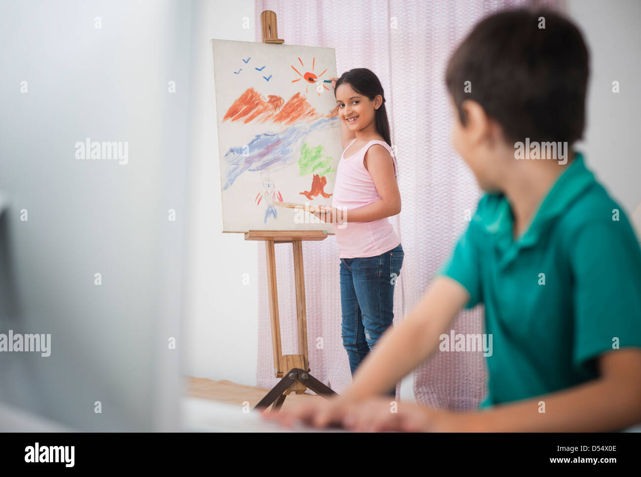 Girl painting on artists canvas with her brother looking at her - Stock Image