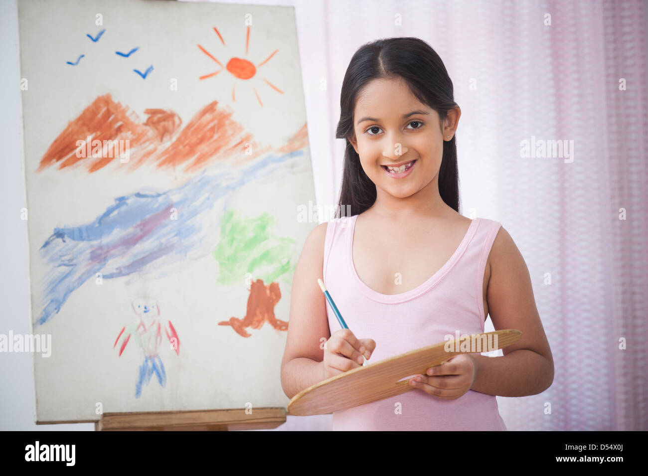 Portrait of a girl painting on artists canvas and smiling - Stock Image
