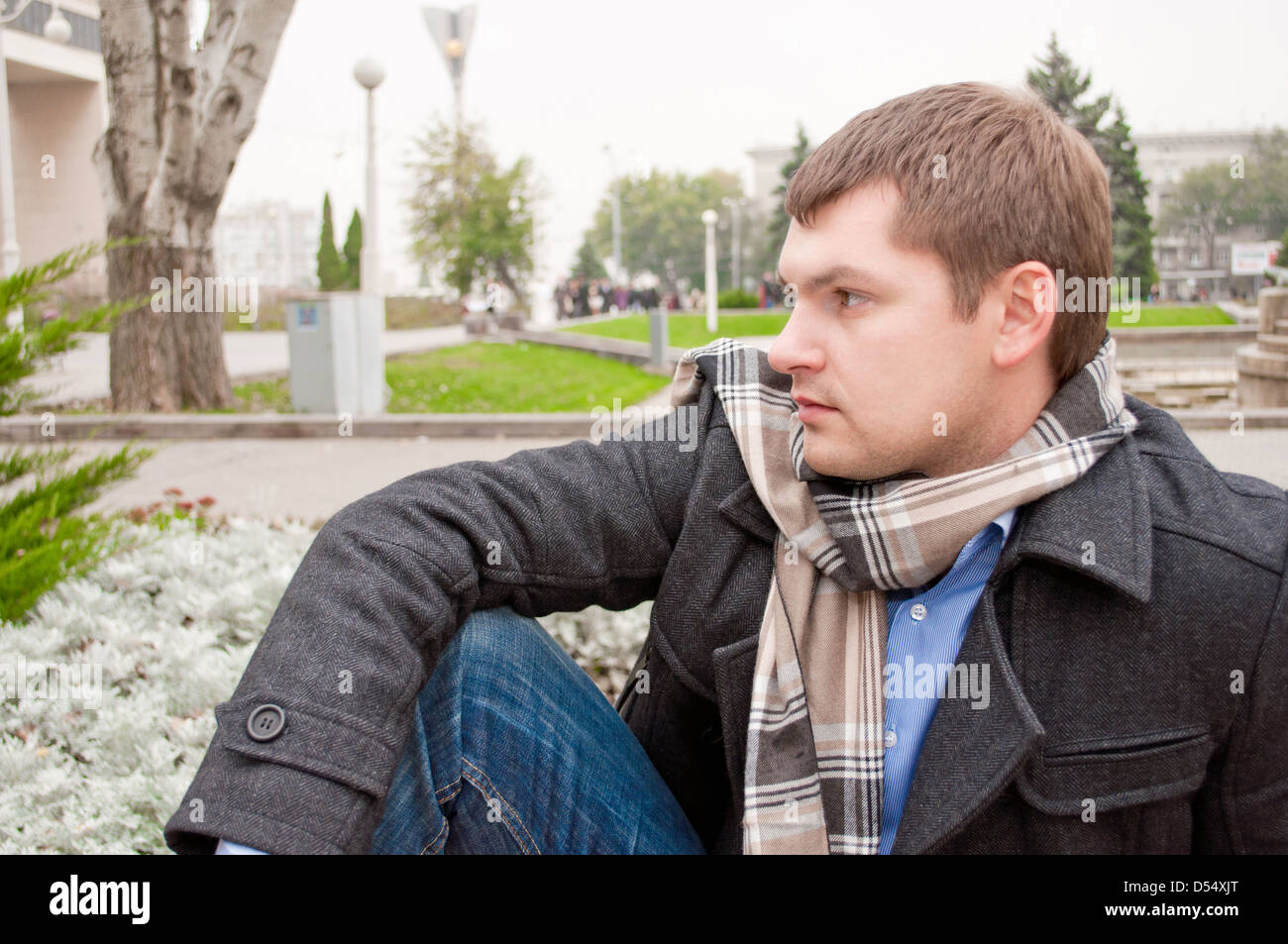 The young human is siting in the autumn park - Stock Image