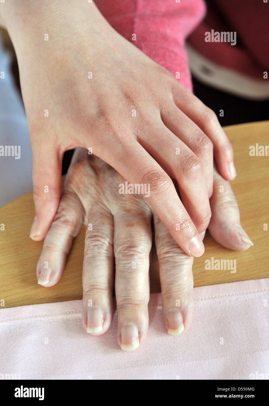 The hand of Hungarian trainee for geriatric nursing, Dora Fekete, touches the hand of 92-year-old Kleopatra Albrecht - Stock Image