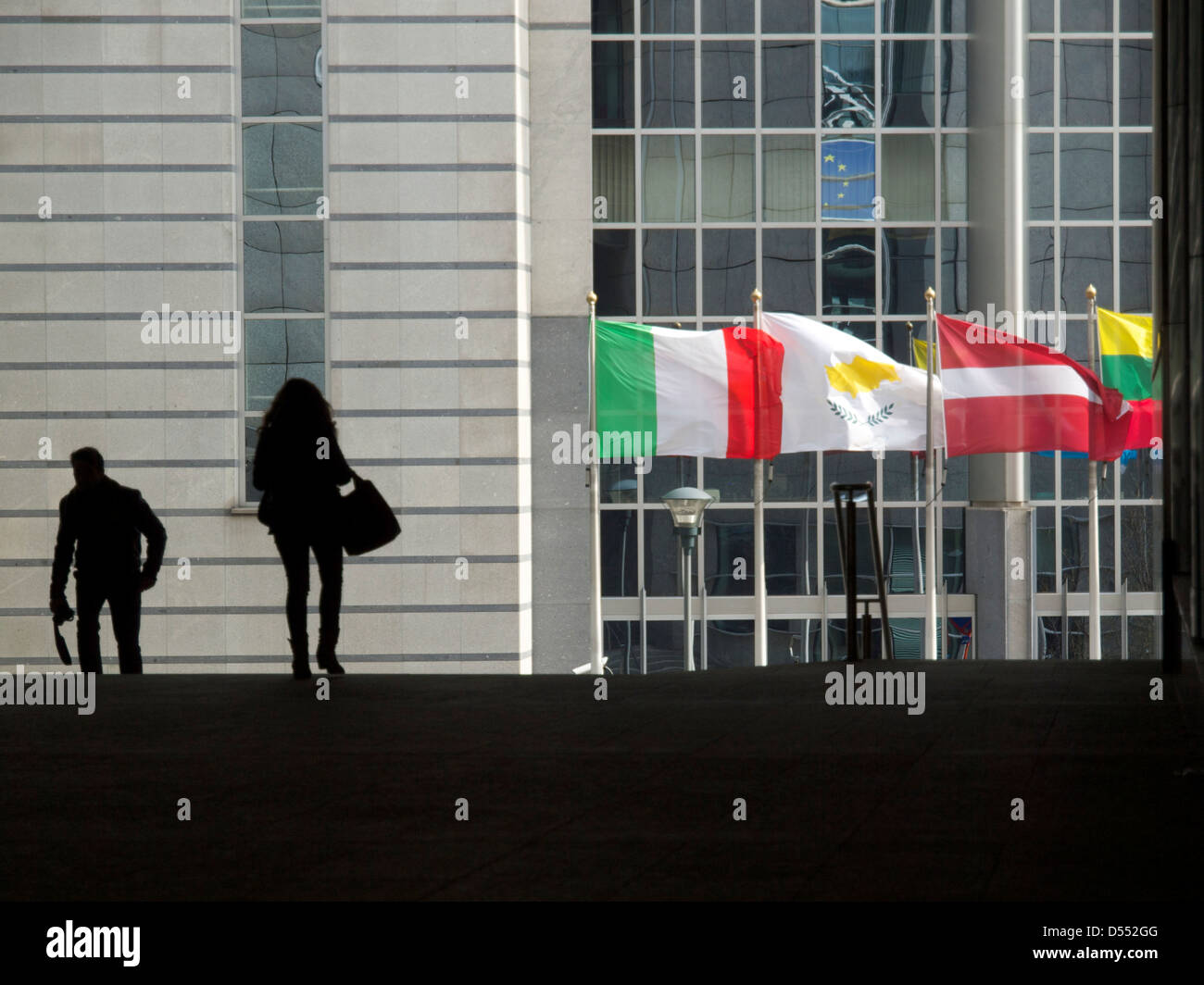 Silhouetted people and colourful flags at the European Parliament building in Brussels, Belgium - Stock Image