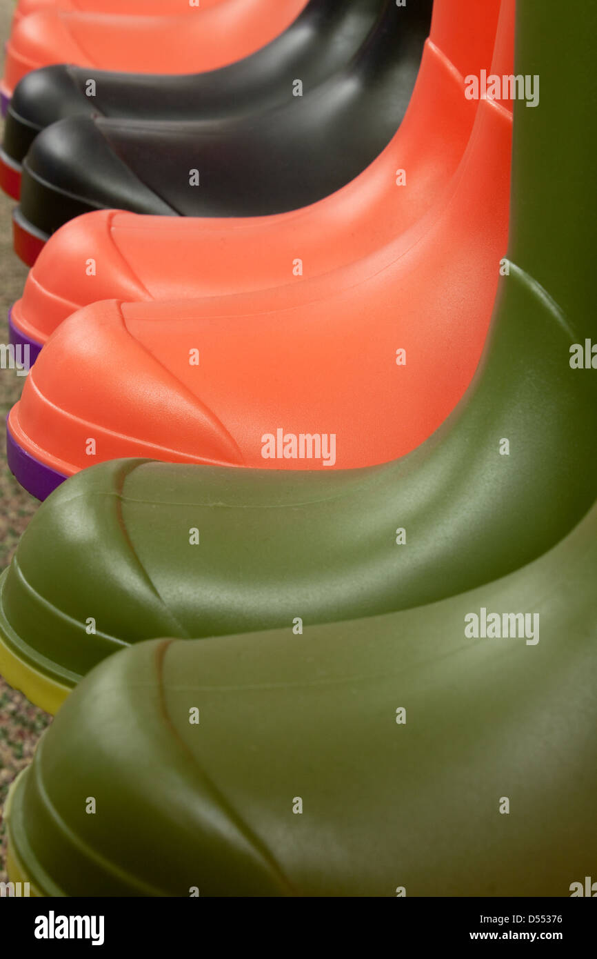 Row of different colored rubber boots on a shelf in a retail outlet selling winter footwear Stock Photo