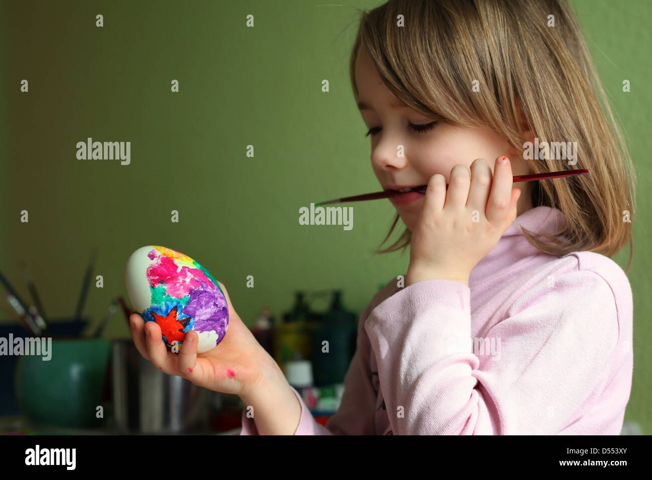 A happy young German girl painting eggs at home for Easter. Leipzig, Germany, Europe. Stock Photo