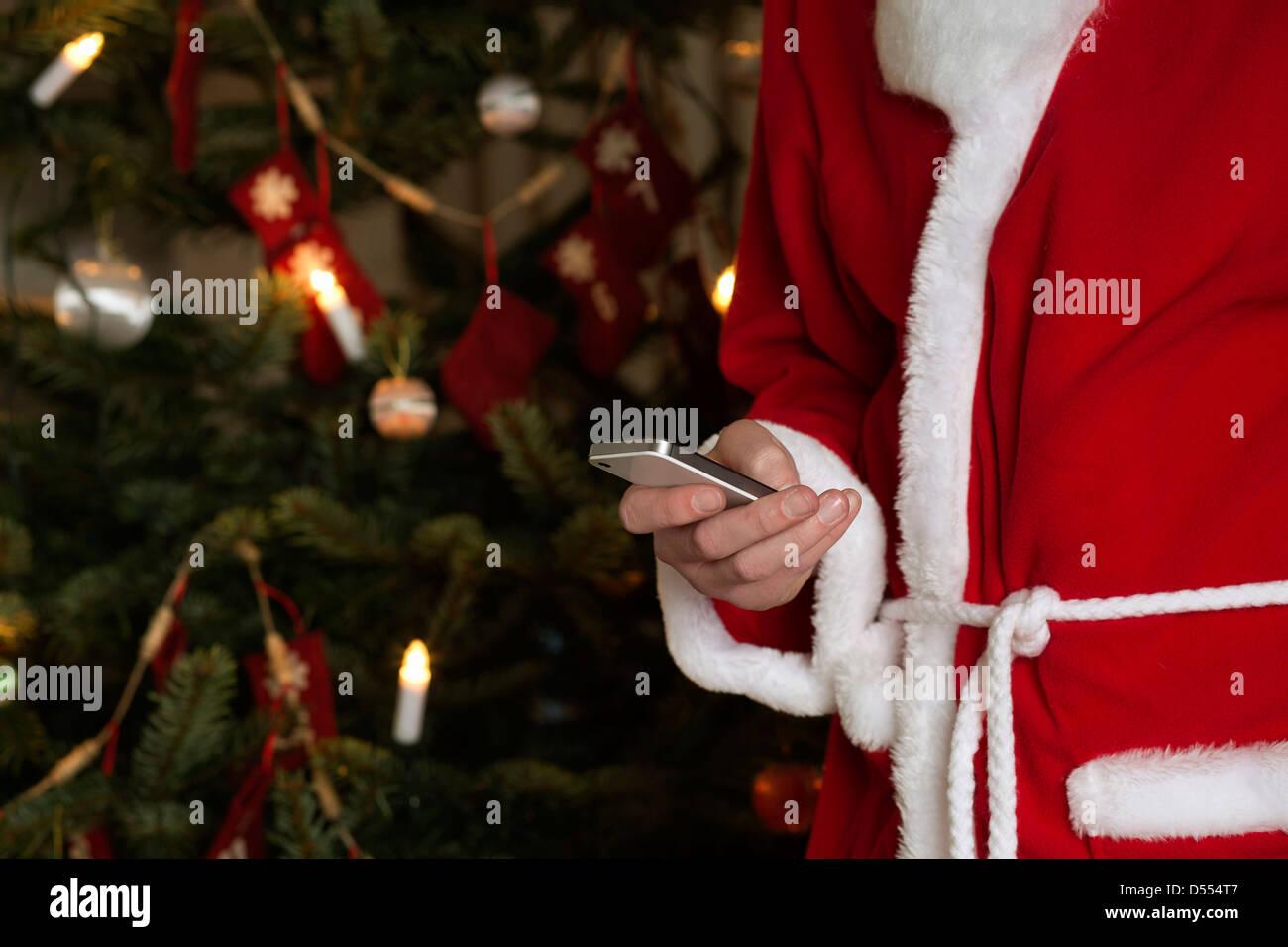 Santa Claus using cell phone - Stock Image