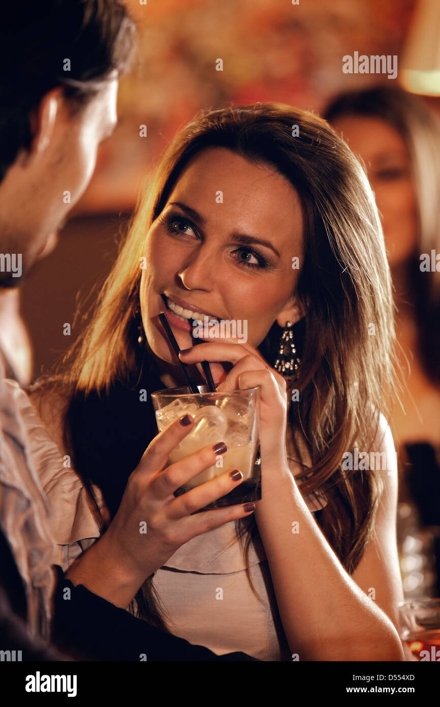Closeup of a beautiful woman at the bar talking with a guy - Stock Image