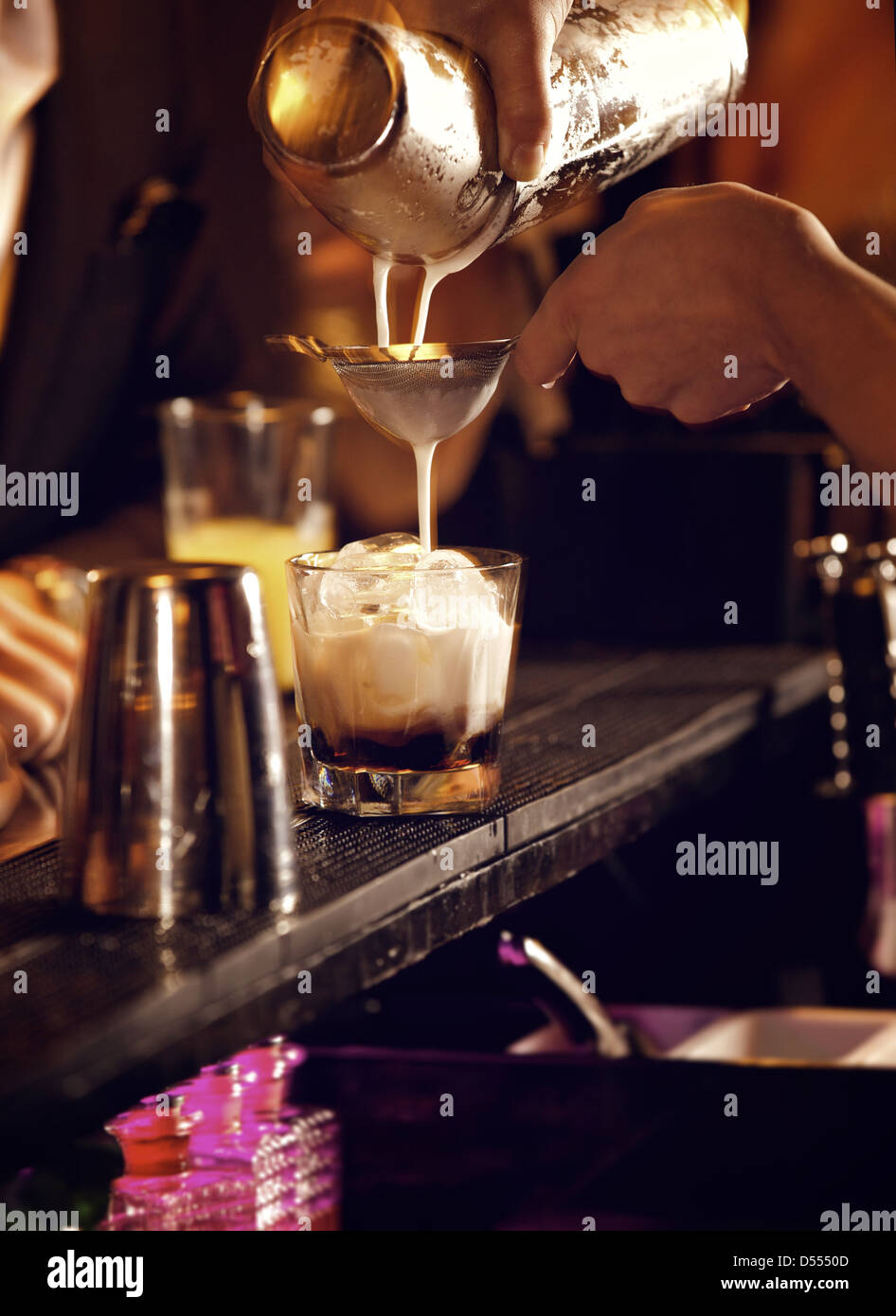 Cold cocktail drink being prepared  by the bartender - Stock Image