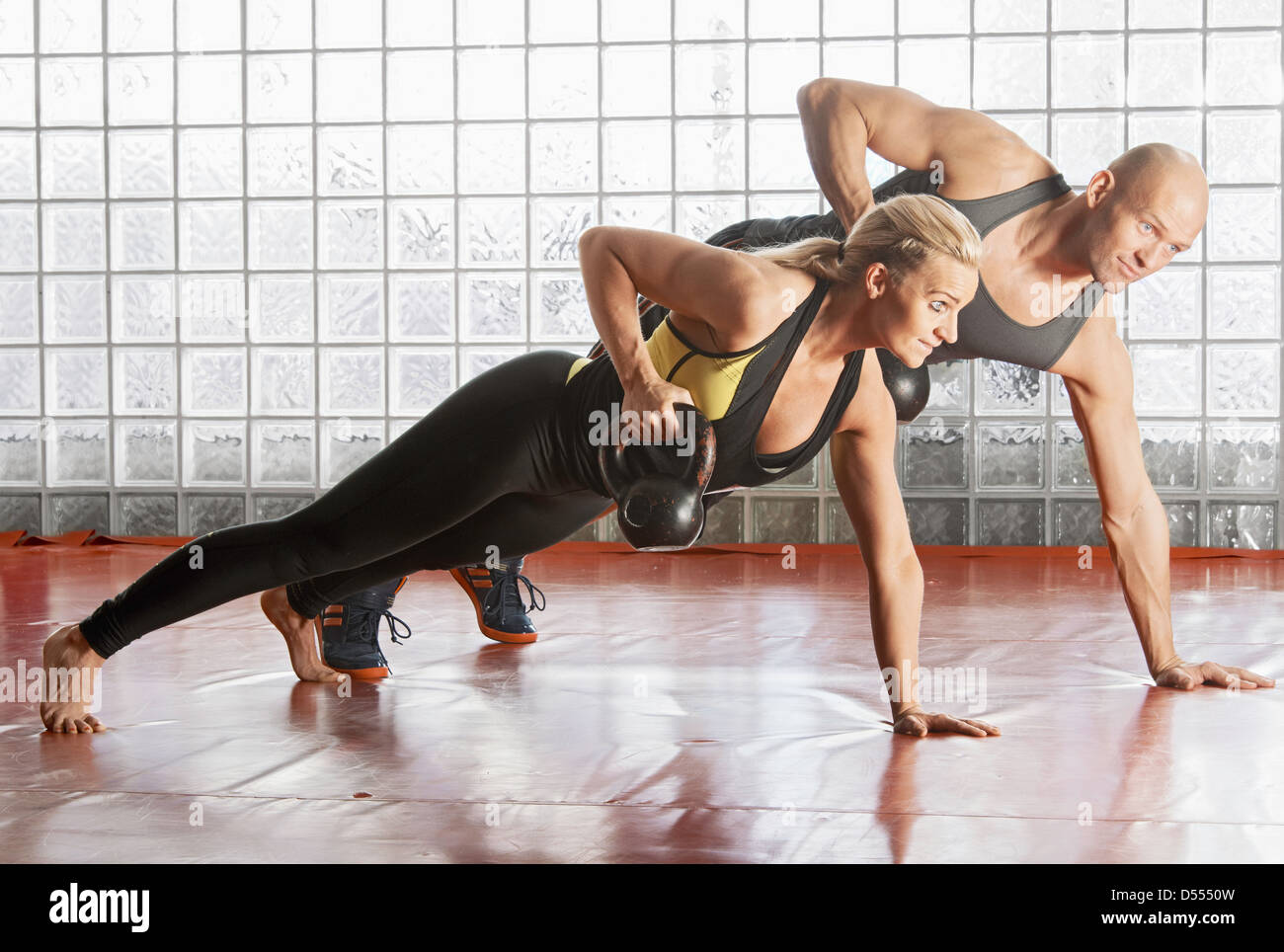 Couple lifting weights in gym - Stock Image