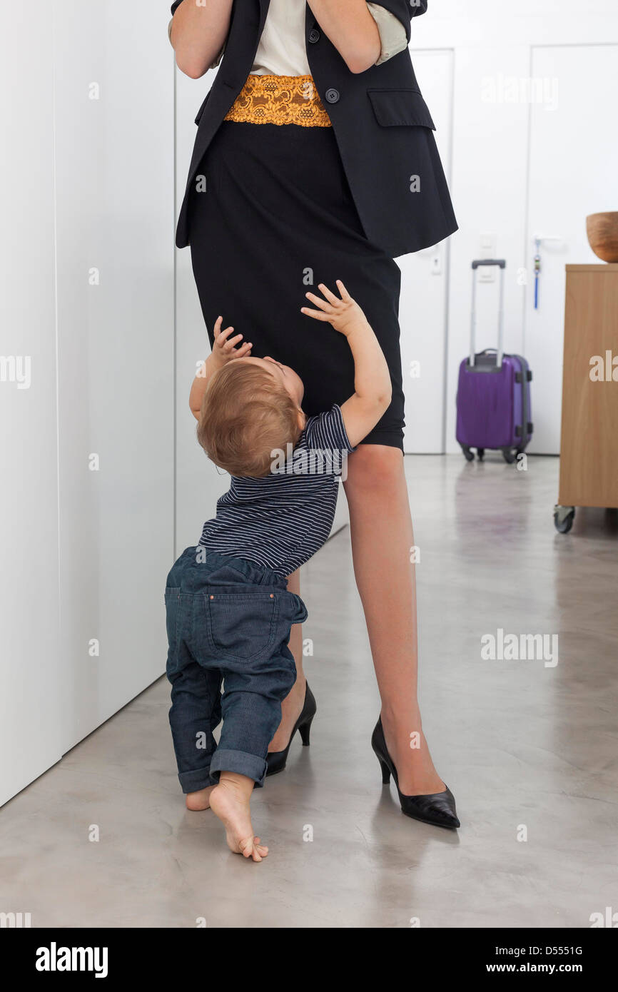 Toddler boy greeting mother in hallway - Stock Image