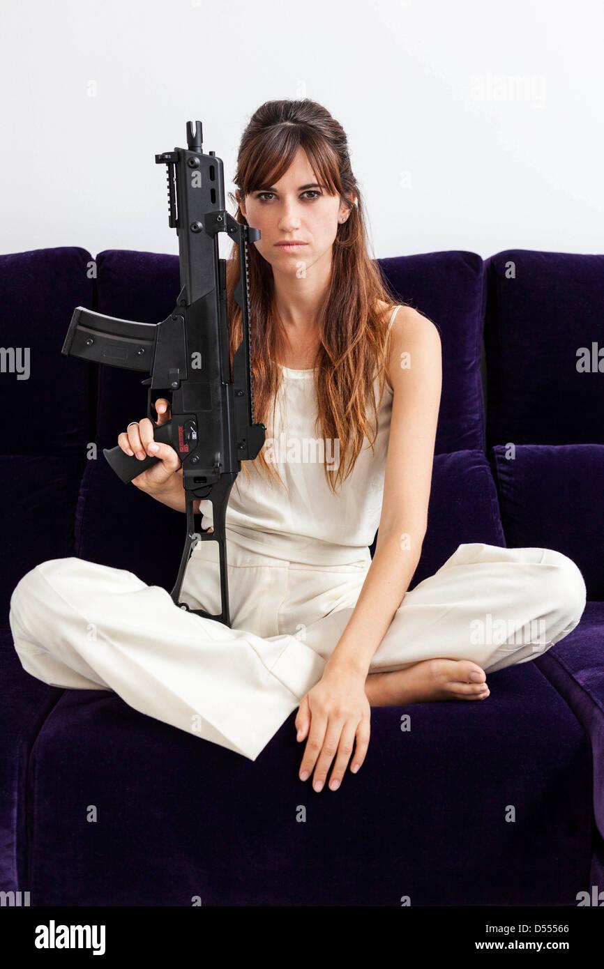 Woman holding machine gun on sofa Stock Photo